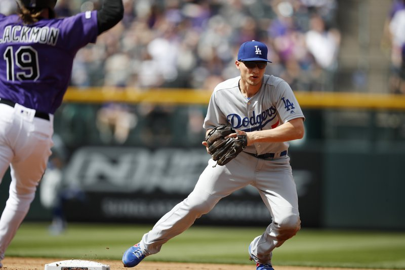 Los Angeles Dodgers shortstop Corey Seager, right, fields the throw to put out Colorado Rockies' Charlie Blackmon at second base on a ground ball hit by David Dahl in the first inning of a baseball game Friday, April 5, 2019, in Denver. (AP Photo/David Zalubowski)