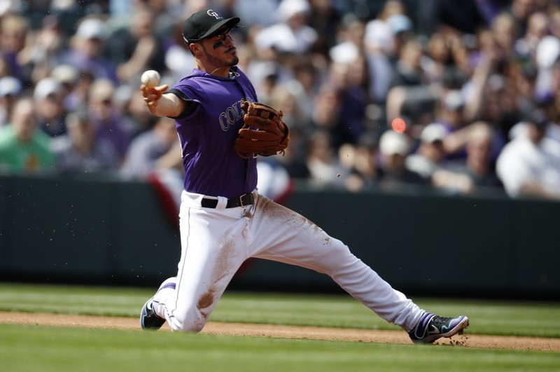 Colorado Rockies third baseman Nolan Arenado throws to second base after fielding a ball hit by Los Angeles Dodgers' Justin Turner in the first inning of a baseball game Friday, April 5, 2019, in Denver. (AP Photo/David Zalubowski)