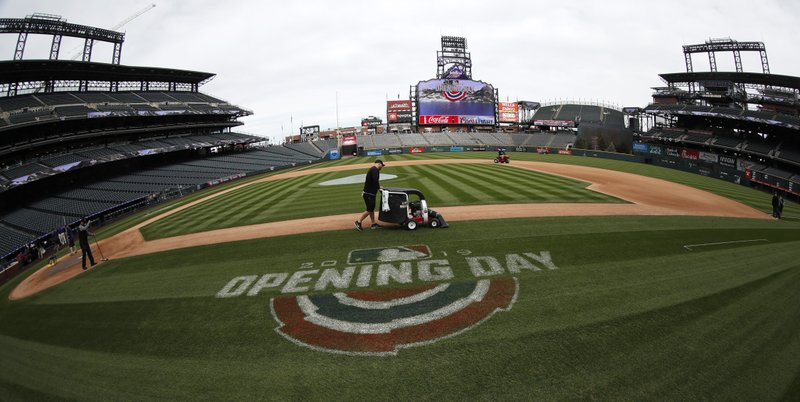 Grounds crew workers toil to prepare the field as the Colorado Rockies host the Los Angeles Dodgers in a baseball game Friday, April 5, 2019, in Denver. (AP Photo/David Zalubowski)