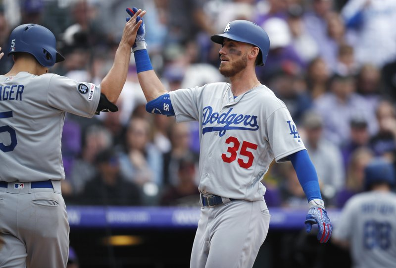 Los Angeles Dodgers' Corey Seager, left, congratulates Cody Bellinger, who crosses home plate after hitting a three-run home run off Colorado Rockies starting pitcher Tyler Anderson during the fifth inning of a baseball game Friday, April 5, 2019, in Denver. (AP Photo/David Zalubowski)