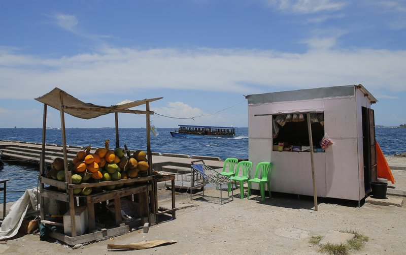 FILE- In this Tuesday, Sept. 25, 2018, file photo, a boat carrying people from a remote atoll arrives to the main boat terminal in Male, Maldives. (AP Photo/Eranga Jayawardena, file)