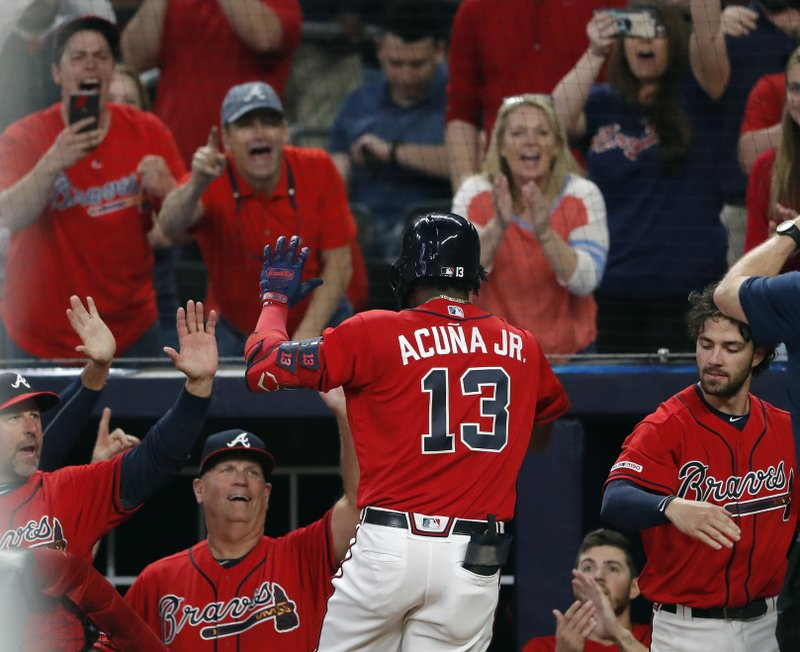 Atlanta Braves' Ronald Acuna Jr. (13) is greeted at the dugout by coach Walt Weiss, left, and manager Brian Snitker after hitting a two-run home run during the fourth inning of the team's baseball game against the Miami Marlins on Friday, April 5, 2019, in Atlanta. (AP Photo/John Bazemore)