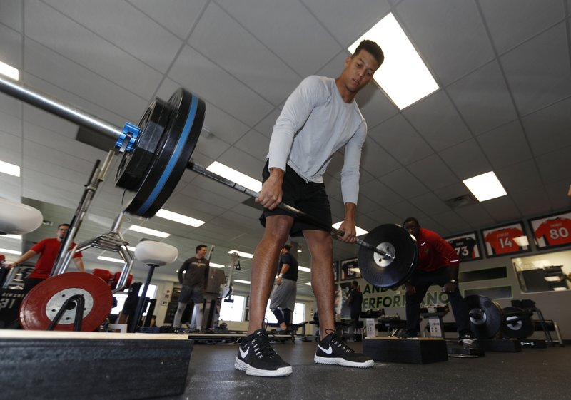 FILE - In this Feb. 16, 2017, file photo, Air Force wide receiver Jalen Robinette lifts weights as he prepares for the NFL combine, at a workout facility in Centennial, Colo. (AP Photo/David Zalubowski, File)