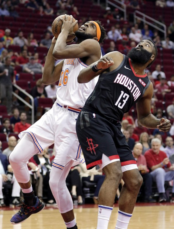 New York Knicks center Mitchell Robinson (26) shoots next to Houston Rockets guard James Harden (13) during the first half of an NBA basketball game Friday, April 5, 2019, in Houston. (AP Photo/Michael Wyke)