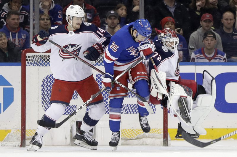 Columbus Blue Jackets goaltender Sergei Bobrovsky, right, of Russia, loses his footing as New York Rangers center Vinni Lettieri (95) attacks during the first period of an NHL hockey game Friday, April 5, 2019, in New York. (14), of Switzerland, helps defend on the play. (AP Photo/Julio Cortez)