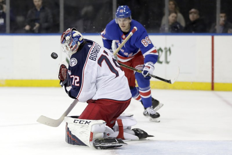 Columbus Blue Jackets goaltender Sergei Bobrovsky, of Russia, blocks a shot from New York Rangers center Mika Zibanejad, not visible, as right wing Pavel Buchnevich (89), of Russia, watches during the second period of an NHL hockey game Friday, April 5, 2019, in New York. (AP Photo/Julio Cortez)