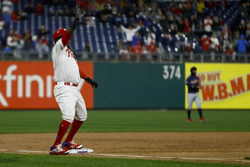 Philadelphia Phillies' Maikel Franco, left, celebrates after hitting a three-run double off Minnesota Twins relief pitcher Ryne Harper and advancing to third, during the first inning of a baseball game Friday, April 5, 2019, in Philadelphia. (AP Photo/Matt Slocum)