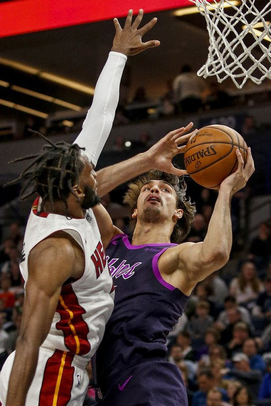 Minnesota Timberwolves forward Dario Saric (36) shoots against Miami Heat forward Justise Winslow (20) in the first quarter of an NBA basketball game Friday, April 5, 2019, in Minneapolis. (AP Photo/Bruce Kluckhohn)