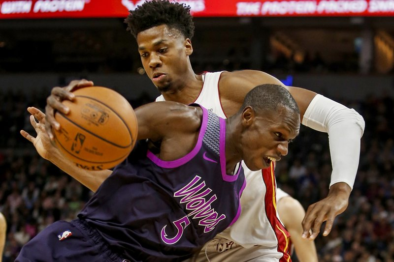 Minnesota Timberwolves center Gorgui Dieng (5) drives to the basket around Miami Heat center Hassan Whiteside, top, in the second quarter of an NBA basketball game Friday, April 5, 2019, in Minneapolis. (AP Photo/Bruce Kluckhohn)