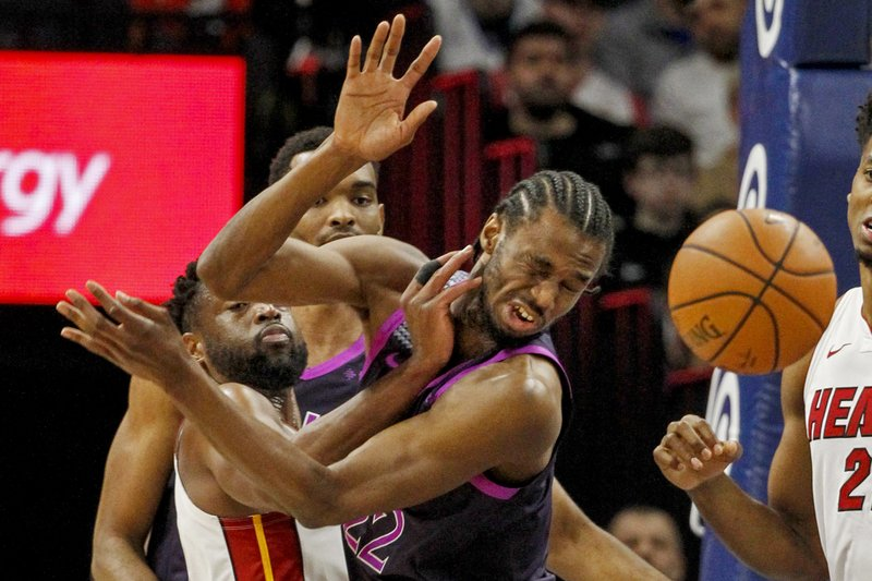 Miami Heat guard Dwyane Wade, front left, knocks the ball away from Minnesota Timberwolves forward Andrew Wiggins (22) in the first quarter of an NBA basketball game Friday, April 5, 2019, in Minneapolis. (AP Photo/Bruce Kluckhohn)