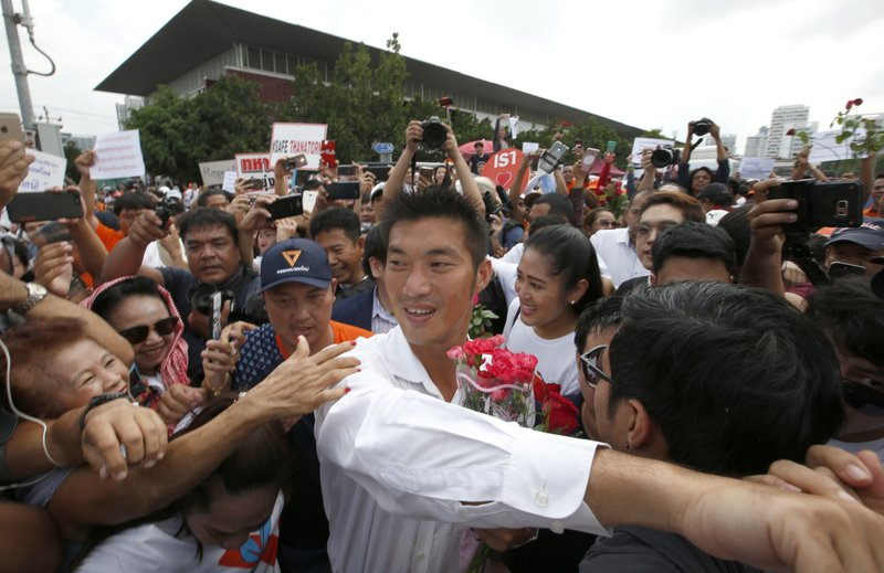Thailand's Future Forward Party leader Thanathorn Juangroongruangkit, center, is mobbed by his supporters upon arrival at a police station Bangkok, Thailand, Saturday, April 6, 2019. (AP Photo/Sakchai Lalit)