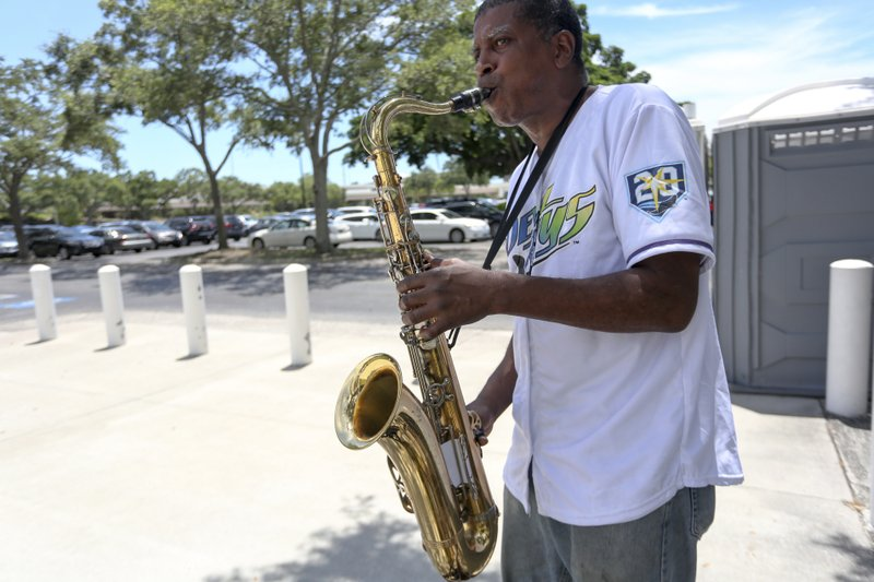 In this June 26, 2018 photo, Max Pierre, 59, plays the saxophone outside Tropicana Field in St. Petersburg, Fla. (Martha Asencio Rhine/Tampa Bay Times via AP)