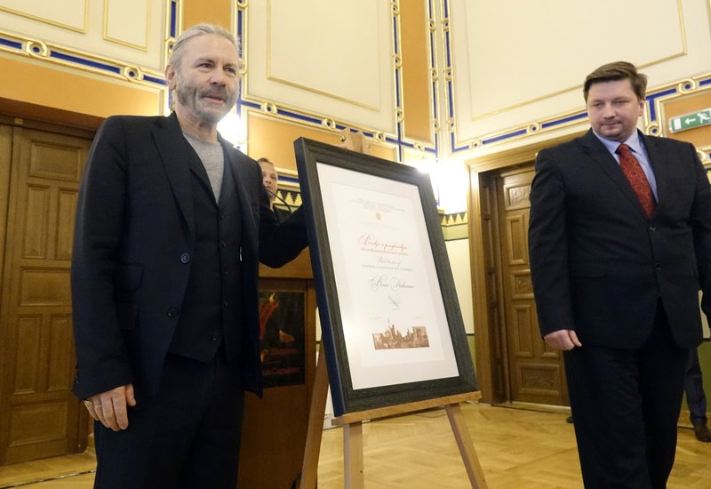 Bruce Dickinson, left, poses with his honorary citizen certificate with Igor Gavric, head of the city assembly at the city hall in Sarajevo, Bosnia-Herzegovina, Saturday, April 6, 2019. (AP Photo/Eldar Emric)