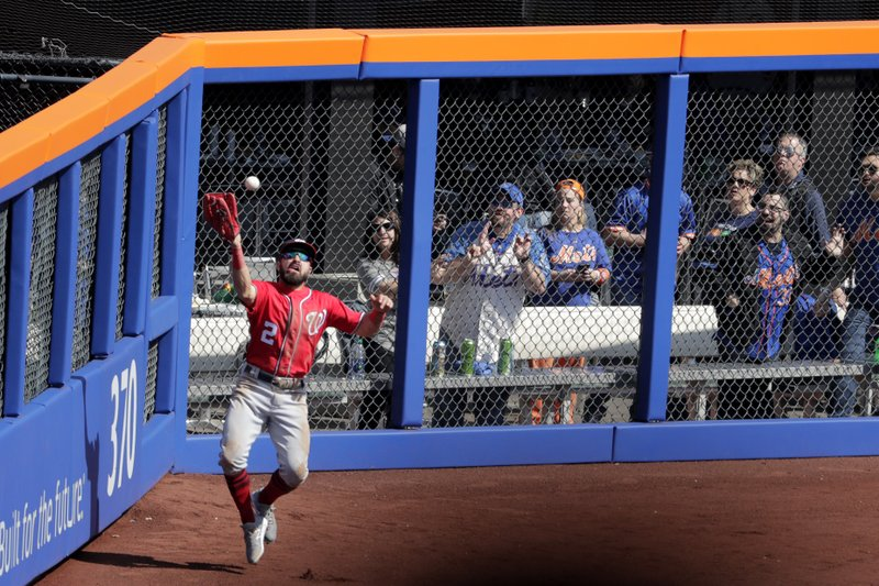 Washington Nationals right fielder Adam Eaton eyes the ball while catching a deep fly ball hit by New York Mets' Wilson Ramos during the sixth inning of a baseball game, Saturday, April 6, 2019, in New York. (AP Photo/Julio Cortez)