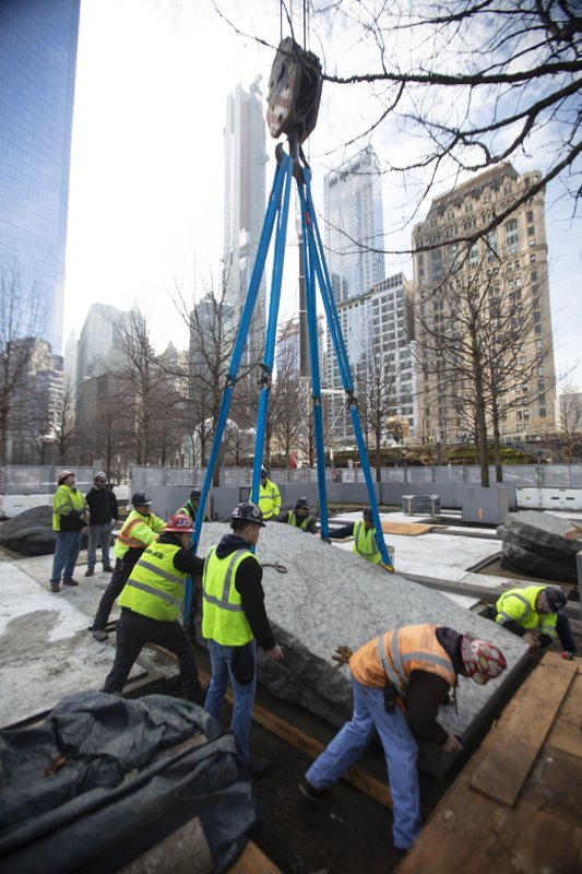 In this photo provided by the 9/11 Memorial & Museum, workers help set large granite monoliths into place as they are lowered by crane, Saturday, April 6, 2019 at the 9/11 Memorial in New York. (Jin S. Lee/ 9/11 Memorial & Museum via AP)