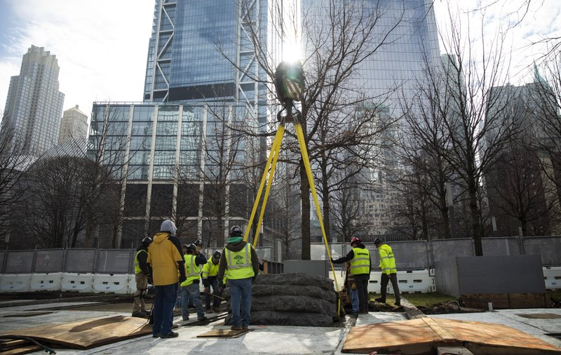 In this photo provided by the 9/11 Memorial & Museum, a 600-ton crane finishes lowering one the granite monoliths to the ground for installation at the 9/11 Memorial, Saturday, April 6, 2019 in New York. (Jin S. Lee/ 9/11 Memorial & Museum via AP)