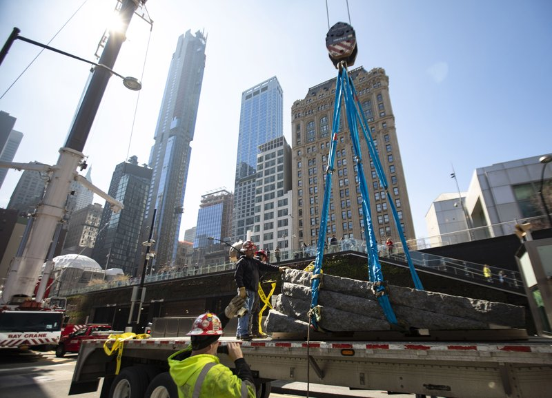 In this photo provided by the 9/11 Memorial & Museum, workers use a 600-ton crane to lift a granite monolith from a flatbed trailer so it can be lowered into the 9/11 Memorial Saturday, April 6, 2019 in New York. (Jin S. Lee / 9/11 Memorial & Museum via AP)