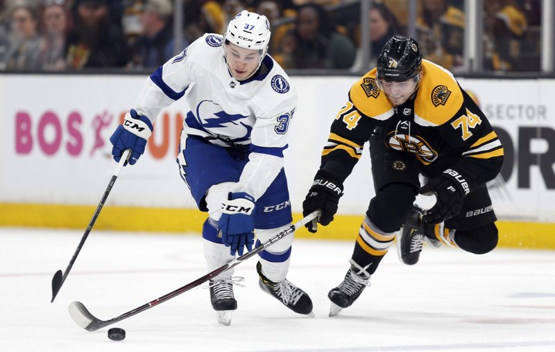 Tampa Bay Lightning's Yanni Gourde (37) and Boston Bruins' Jake DeBrusk (74) battle for the puck during the third period of an NHL hockey game in Boston, Saturday, April 6, 2019. (AP Photo/Michael Dwyer)