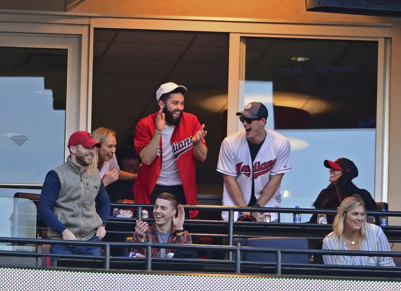 Cleveland Browns quarterback Baker Mayfield, center, watches the seventh inning of a baseball game between the Cleveland Indians and the Toronto Blue Jays, Saturday, April 6, 2019, in Cleveland. (AP Photo/David Dermer)