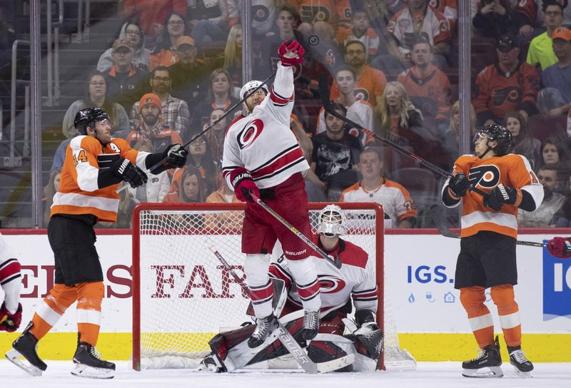 Carolina Hurricanes' Jaccob Slavin leaps to knock the puck away from goalie Curtis McElhinney as Philadelphia Flyers' Sean Couturier, left, and Travis Konecny, right, reach up with their sticks during the third period of an NHL hockey game, Saturday, April 6, 2019, in Philadelphia. (AP Photo/Chris Szagola)