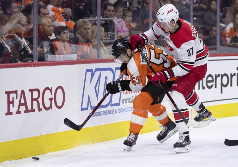 Philadelphia Flyers' Shayne Gostisbehere, left, and Carolina Hurricanes' Andrei Svechnikov go after the puck during the third period of an NHL hockey game Saturday, April 6, 2019, in Philadelphia. (AP Photo/Chris Szagola)