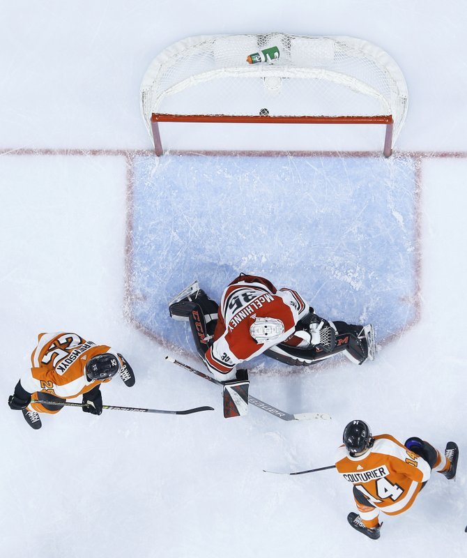 Philadelphia Flyers' Sean Couturier, right, shoots the puck past Carolina Hurricanes' Curtis McElhinney, center, for a goal during the second period of an NHL hockey game Saturday, April 6, 2019, in Philadelphia. (AP Photo/Chris Szagola)