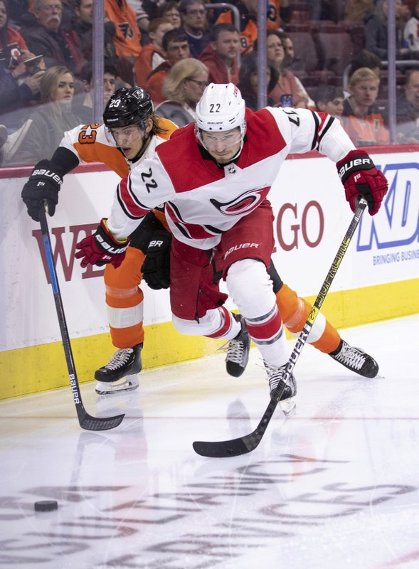 Carolina Hurricanes' Brett Pesce, right, goes after the puck with Philadelphia Flyers' Oskar Lindblom trailing during the second period of an NHL hockey game Saturday, April 6, 2019, in Philadelphia. (AP Photo/Chris Szagola)