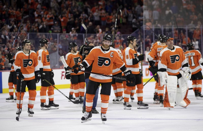 Philadelphia Flyers' Claude Giroux, center, and teammates skate off the ice after thanking the fans following the team's NHL hockey game against the Carolina Hurricanes, Saturday, April 6, 2019, in Philadelphia. (AP Photo/Chris Szagola)