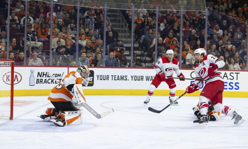 Carolina Hurricanes' Justin Faulk, right, shoots the puck past Philadelphia Flyers' Carter Hart, left, for a goal during the first period of an NHL hockey game Saturday, April 6, 2019, in Philadelphia. (AP Photo/Chris Szagola)