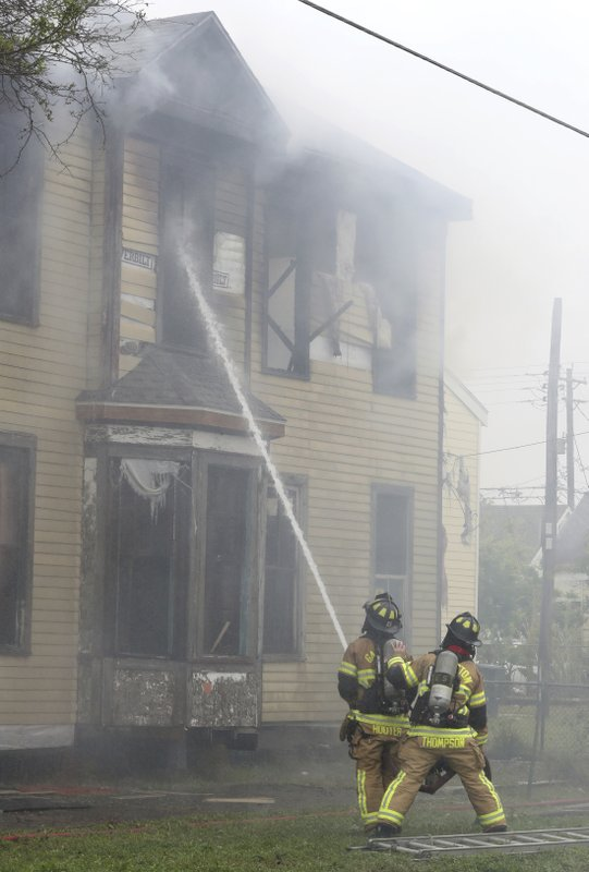 In this Friday, April 5, 2019 photo, Galveston firefighters douse the second floor and attic of a house on Avenue K at 29th Street in Galveston, Texas. (Jennifer Reynolds/The Galveston County Daily News via AP)