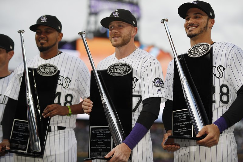 From left, Colorado Rockies starting pitcher German Marquez, Colorado Rockies shortstop Trevor Story and Colorado Rockies third baseman Nolan Arenado hold up their Silver Slugger awards during a ceremony before a baseball game against the Los Angeles Dodgers Saturday, April 6, 2019, in Denver. (AP Photo/David Zalubowski)