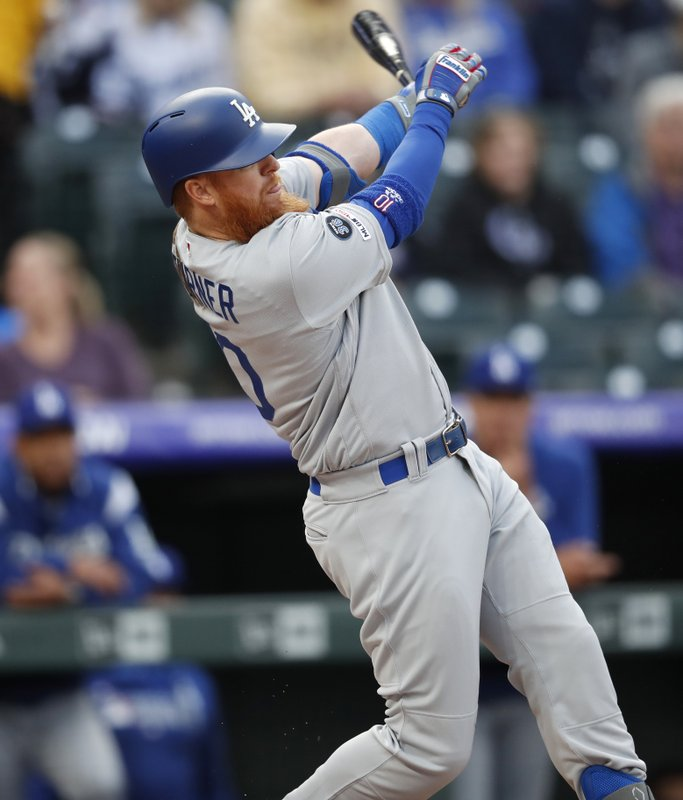 Los Angeles Dodgers' Justin Turner follows the flight of his single off Colorado Rockies starting pitcher Jon Gray in the first inning of a baseball game Saturday, April 6, 2019, in Denver. (AP Photo/David Zalubowski)
