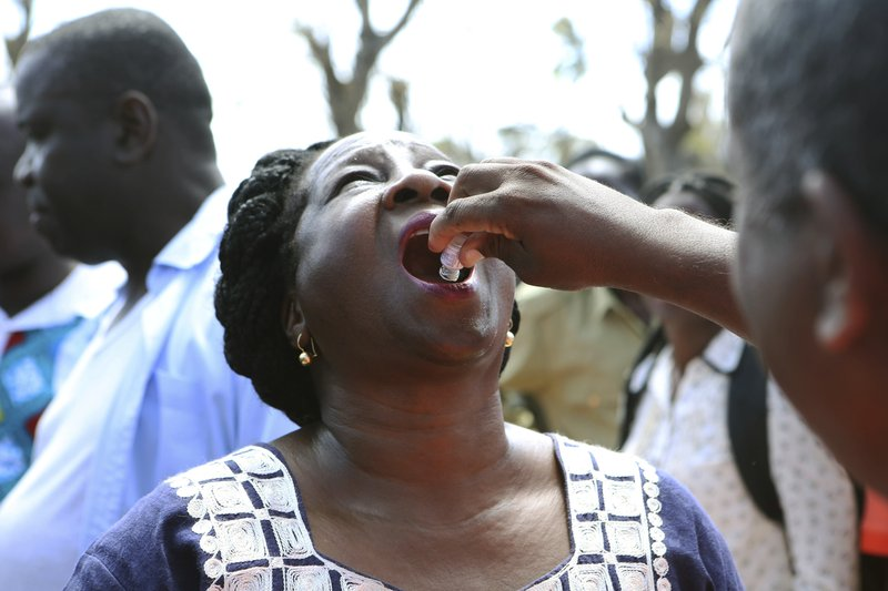 A government official receives an oral cholera vaccination at a camp for displaced survivors of cyclone Idai in Beira, Mozambique, Wednesday, April, 3, 2019. (AP Photo/Tsvangirayi Mukwazhi)