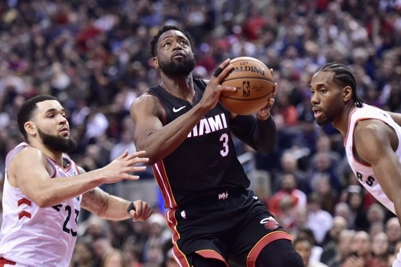 Miami Heat guard Dwyane Wade (3) drives to net past Toronto Raptors guard Fred VanVleet (23) and forward Kawhi Leonard (2) during second half NBA basketball action in Toronto on Sunday, April 7, 2019. (Frank Gunn/The Canadian Press via AP)