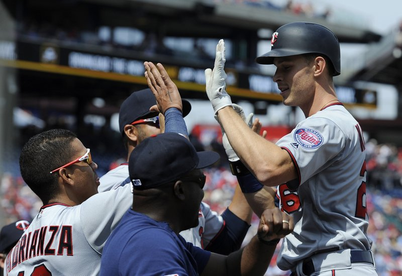 Minnesota Twins' Max Kepler, right, celebrates with Ehire Adrianza, left, after hitting a solo home run in the first inning of a baseball game against the Philadelphia Phillies, Sunday, April 7, 2019, in Philadelphia. (AP Photo/Michael Perez)