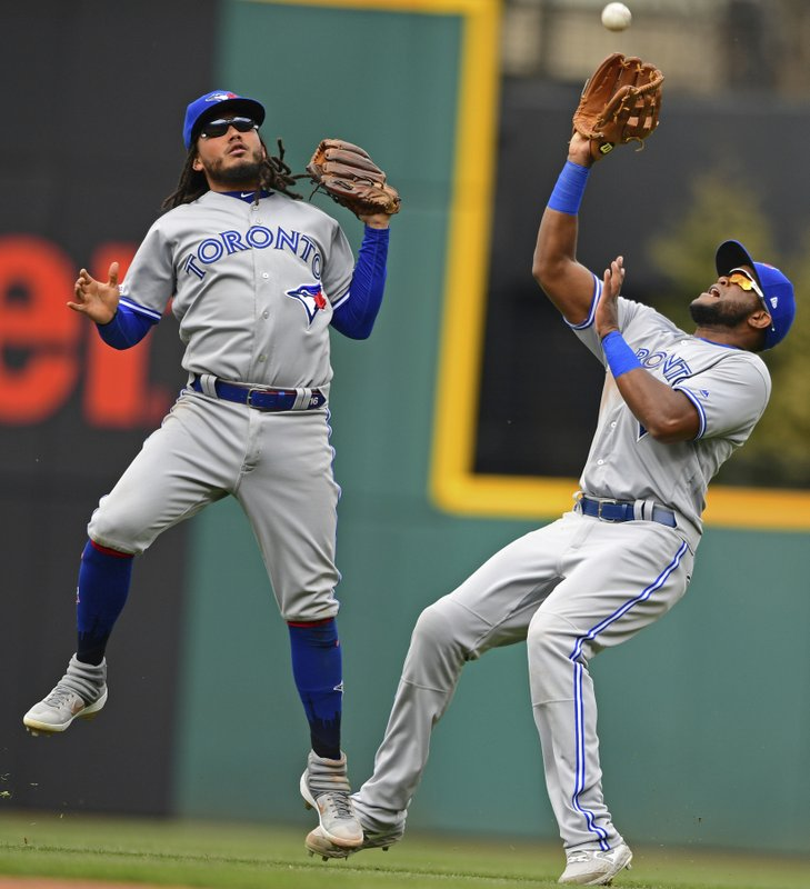 Toronto Blue Jays' Socrates Brito, right, avoids colliding with Freddy Galvis to catch a ball hit by Cleveland Indians' Kevin Plawecki in the fourth inning of a baseball game, Sunday, April 7, 2019, in Cleveland. (AP Photo/David Dermer)