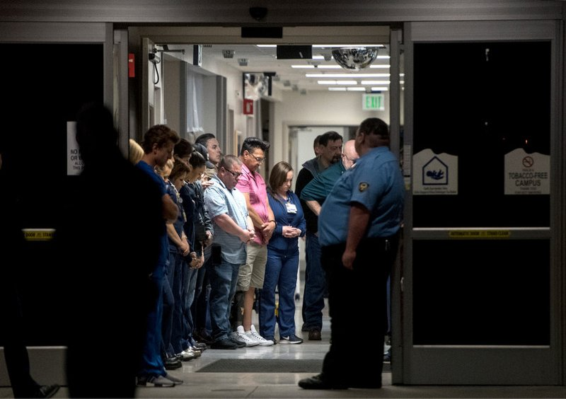 In this Saturday, April 7, 2019 photo, emergency hospital staff bow their heads in a sea of salutes for fallen California Highway Patrol motorcycle officer Sgt. (Cindy Yamanaka/The Orange County Register via AP)