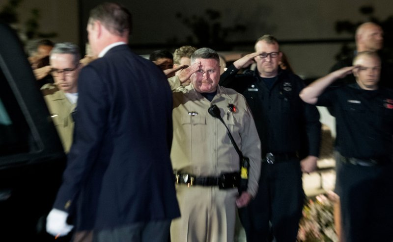 In this Saturday, April 6, 2019 photo, after carrying the casket of fallen CHP Sgt. Steve Licon, an unidentified law enforcement agent, center, doesn't take his eye off Sgt. (Cindy Yamanaka/The Orange County Register via AP)/The Orange County Register via AP)