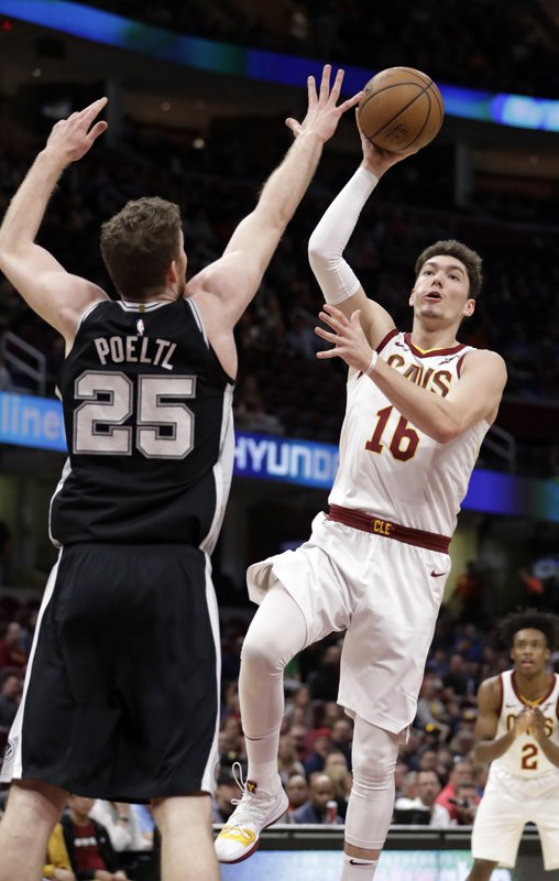 Cleveland Cavaliers' Cedi Osman (16) drives to the basket against San Antonio Spurs' Jakob Poeltl (25) in the first half of an NBA basketball game, Sunday, April 7, 2019, in Cleveland. (AP Photo/Tony Dejak)