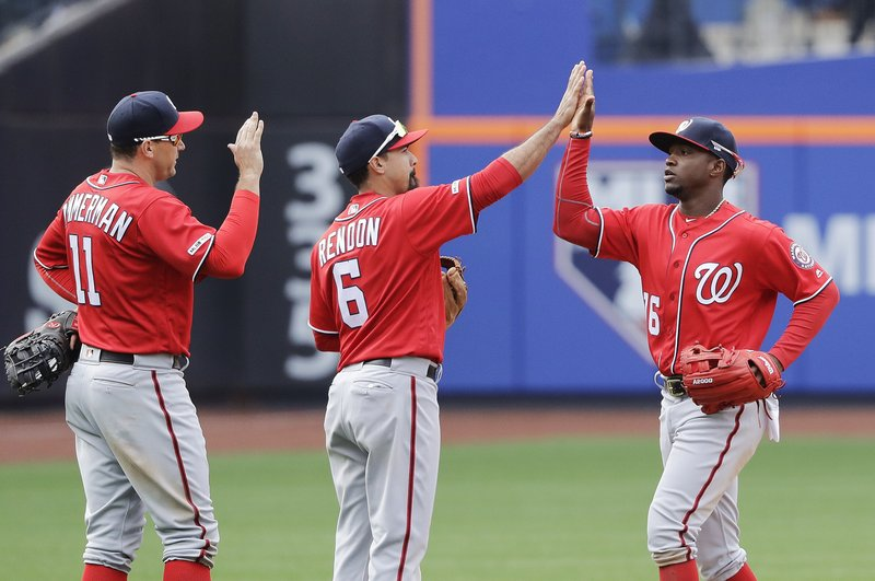 Washington Nationals' Ryan Zimmerman (11), Anthony Rendon (6) and Victor Robles celebrates after the team's baseball game against the New York Mets on Sunday, April 7, 2019, in New York. (AP Photo/Frank Franklin II)