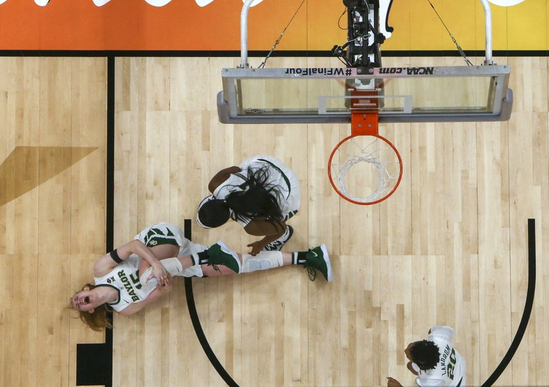 Baylor forward Lauren Cox (15) grabs her knee as teammates Kalani Brown (21) and  Juicy Landrum (20) watch after Cox was injured during the second half against Notre Dame in the Final Four championship game of the NCAA women's college basketball tournament Sunday, April 7, 2019, in Tampa, Fla. (Dirk Shadd/Tampa Bay Times via AP)