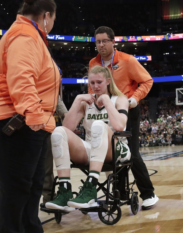 Baylor forward Lauren Cox is assisted off the court after she injured her knee during the second half of the team's Final Four championship game against Notre Dame in the NCAA women's college basketball tournament Sunday, April 7, 2019, in Tampa, Fla. (AP Photo/John Raoux)