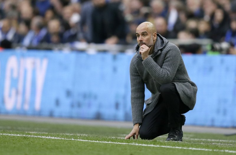 Manchester City coach Pep Guardiola watches from the touchline during the English FA Cup semifinal soccer match between Manchester City and Brighton & Hove Albion at Wembley Stadium in London, Saturday, April 6, 2019. (AP Photo/Tim Ireland)
