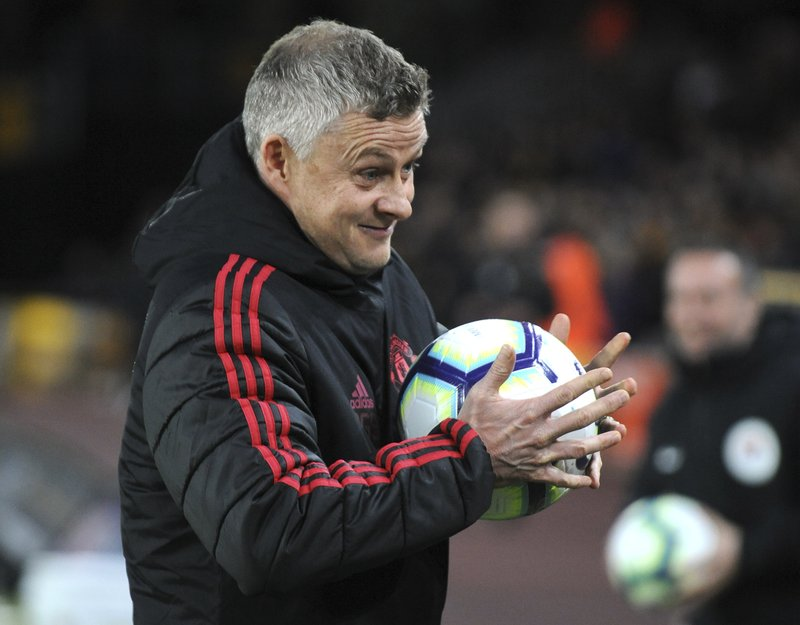 Manchester United manager Ole Gunnar Solskjaer holds a ball before the start of the English Premier League soccer match between Wolverhampton Wanderers and Manchester United at the Molineux Stadium in Wolverhampton, England, Tuesday, April 2, 2019. (AP Photo/Rui Vieira)