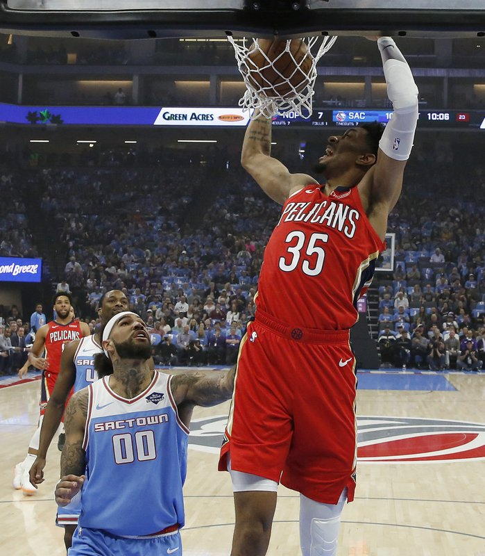 New Orleans Pelicans forward Christian Wood dunks as Sacramento Kings center Willie Cauley-Stein watches during the first half of an NBA basketball game Sunday, April 7, 2019, in Sacramento, Calif. (AP Photo/Rich Pedroncelli)