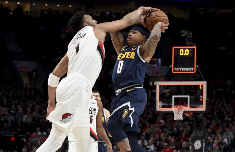 Portland Trail Blazers guard Evan Turner, left, blocks the shot of Denver Nuggets guard Isaiah Thomas at the end of the first quarter of an NBA basketball game in Portland, Ore. (AP Photo/Steve Dykes)