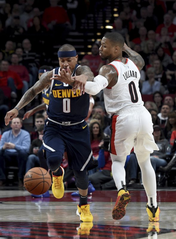 Denver Nuggets guard Isaiah Thomas, left, knocks the ball away from Portland Trail Blazers guard Damian Lillard during the first half of an NBA basketball game in Portland, Ore. (AP Photo/Steve Dykes)