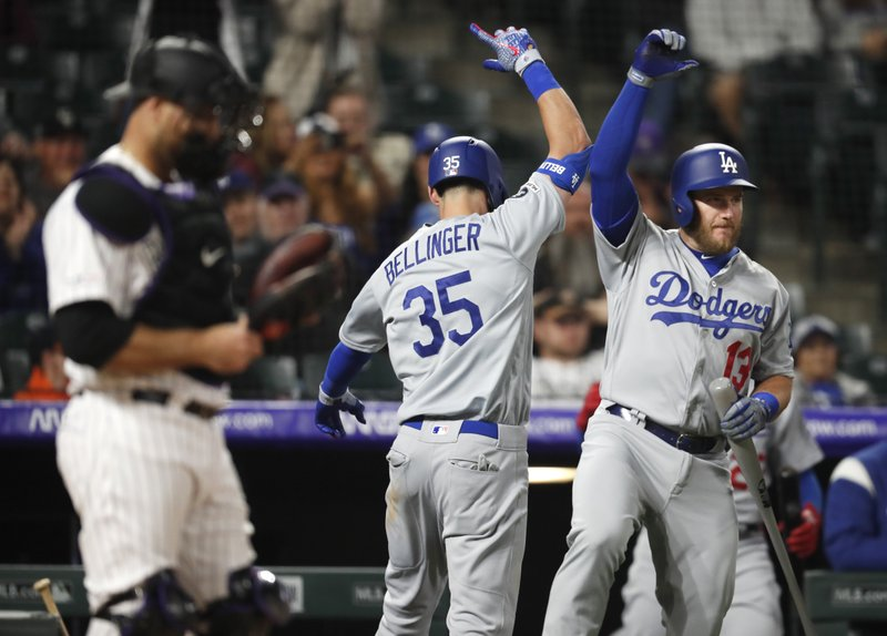 Los Angeles Dodgers' Cody Bellinger, center, celebrates hitting a solo home run with Max Muncy, right, as Colorado Rockies catcher Chris Iannetta stands in the foreground in the eighth inning of a baseball game Sunday, April 7, 2019, in Denver. (AP Photo/David Zalubowski)