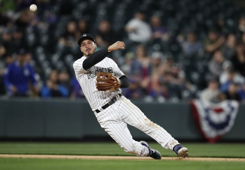 Colorado Rockies third baseman Nolan Arenado throws to first base to put out Los Angeles Dodgers' Dennis Santana in the eighth inning of a baseball game Sunday, April 7, 2019, in Denver. (AP Photo/David Zalubowski)