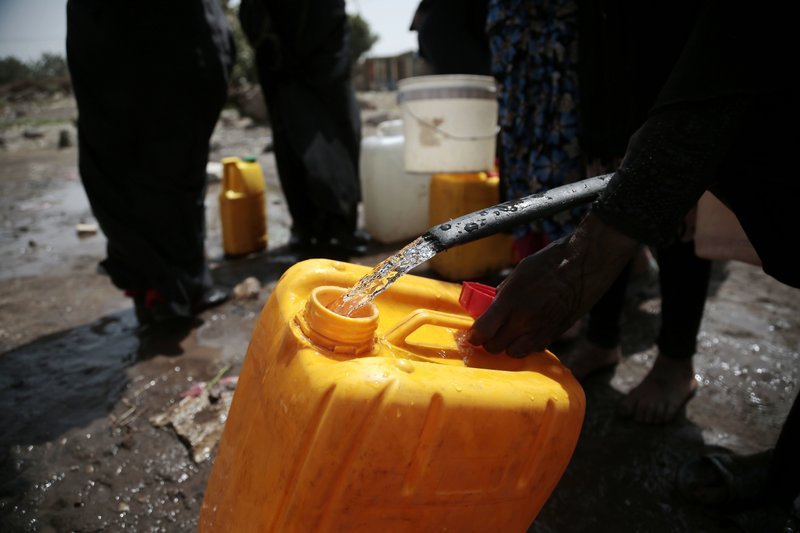 FILE - In this July 12, 2017 file photo, a woman fills a jerrycan with water from a well that is alleged to be contaminated with the bacterium Vibrio cholera, on the outskirts of Sanaa, Yemen. (AP Photo/Hani Mohammed, File)